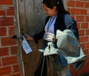 Agente de endemias afixa recado em porta de casa no Padre Ulrico; bairro é um dos que mais preocupa, apesar do controle da doença