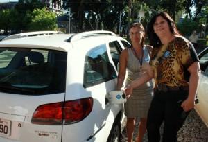 A secretária de Saúde, Rose Mari Guarda, e a diretora da Vigilância em Saúde, Bernadete de Souza, com carro adesivado na tampa do tanque de combustível