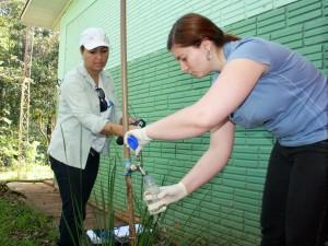 As biólogas Raphaela França e Carla Grellmann, da Funasa, recolhem amostra de água na Secção Jacaré