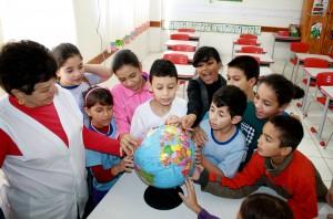 Com a professora Maria Raitz, alunos procuram no globo alguns dos países que disputarão a Copa no Brasil