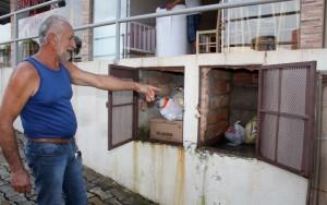 Seu Inir mostra o local que construiu para armazenar o lixo após ser notificado; 'casinha' organiza acondicionamento de resíduos e evita atração de insetos e roedores