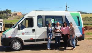 O motorista João dos Santos recebe a chave da nova van de Edinéia Benini, Rose Guarda e Dalva Zago